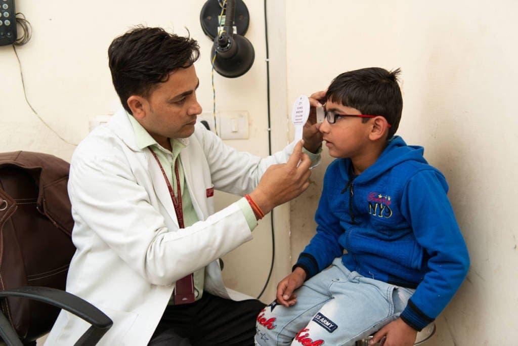 एक  चिकित्सक एक बच्चे की आँखों की जांच करते हुए