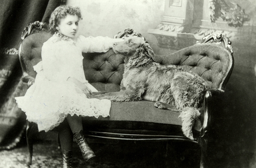Helen Keller as a young girl, sitting on a couch, her large dog Jumbo sitting next to her.