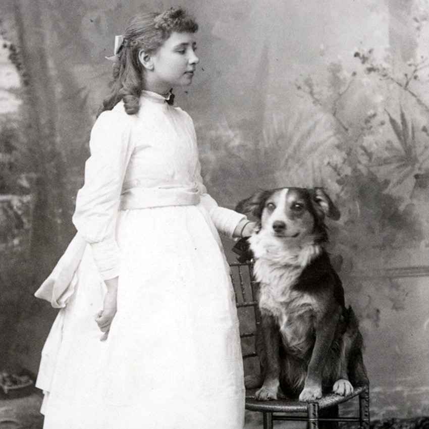 A young Helen Keller standing next to a dog seated in a chair.