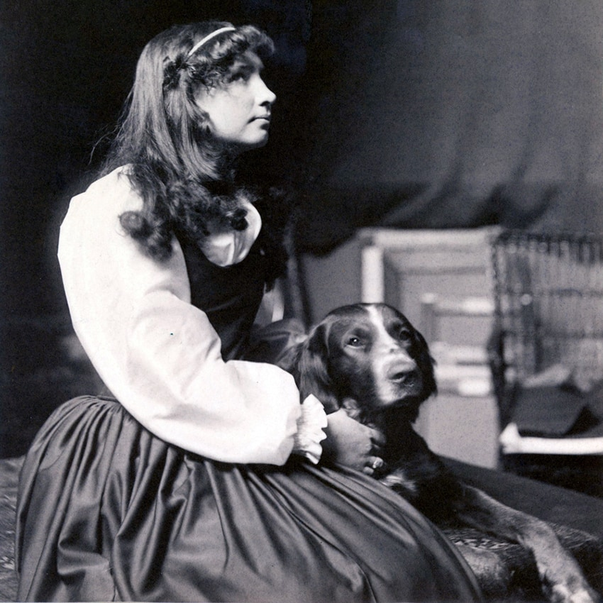 Helen Keller as an adolescent, sitting in profile with a dog sitting next to her.