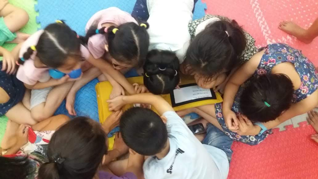 A group of young children with visual impairment in Vietnam reach out to feel a page in a tactile book.