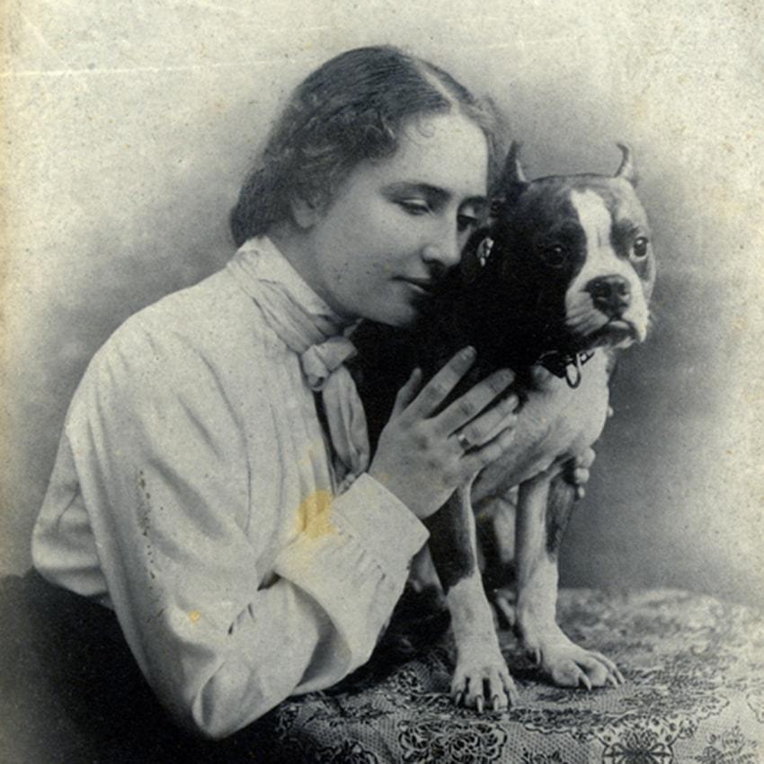 Helen Keller pressing her face against the side of small Boston bull terrier named Phiz.