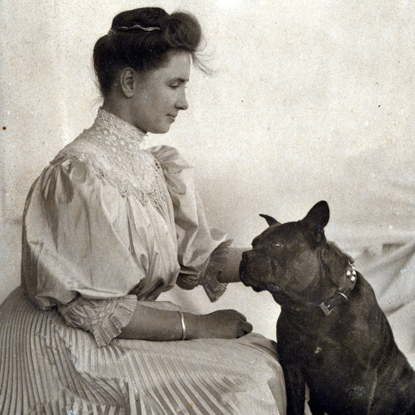 Helen Keller leans forward to pet a small black dog at her right.