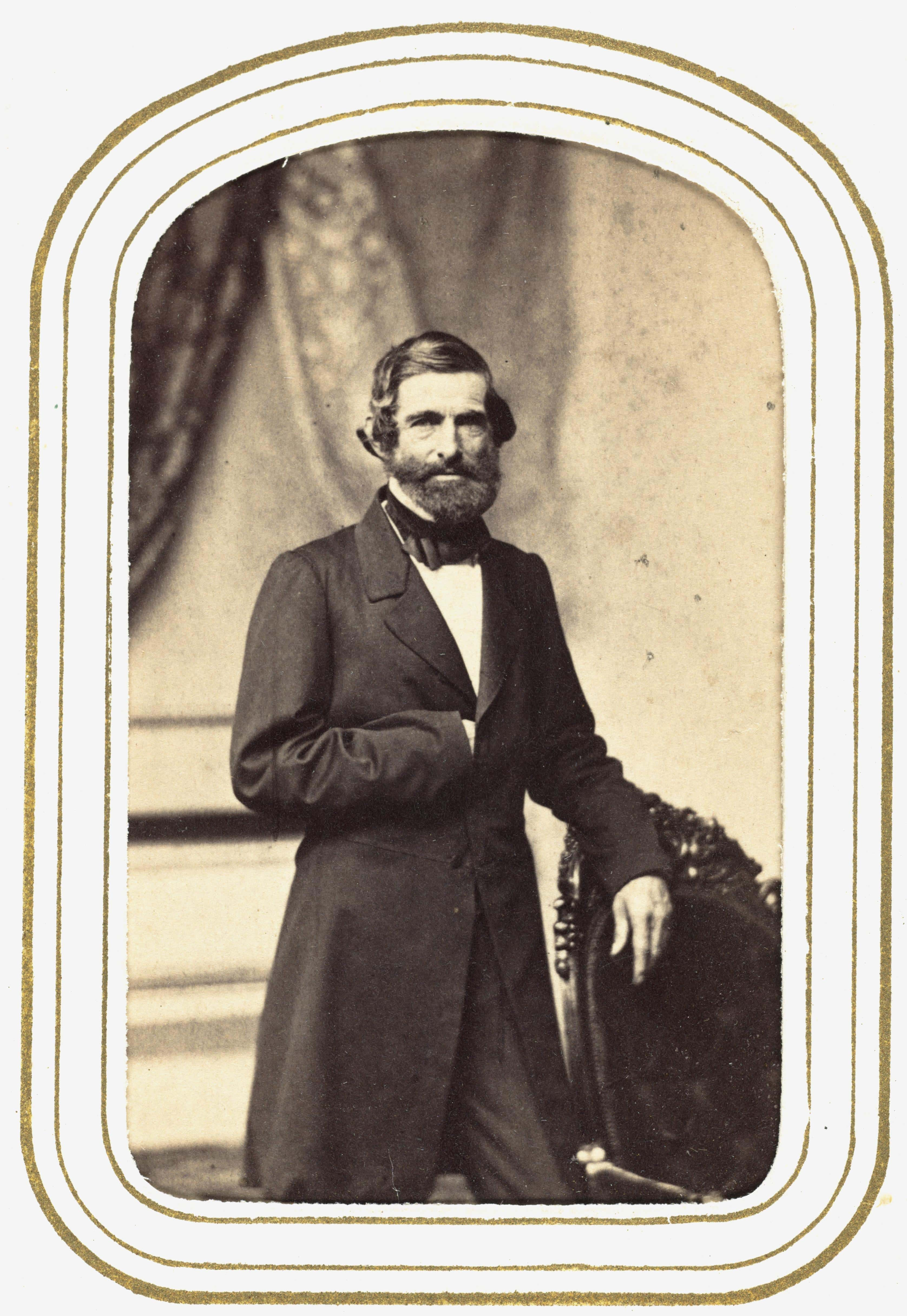 Portrait of Samuel Gridley Howe standing with one arm tucking inside coat.