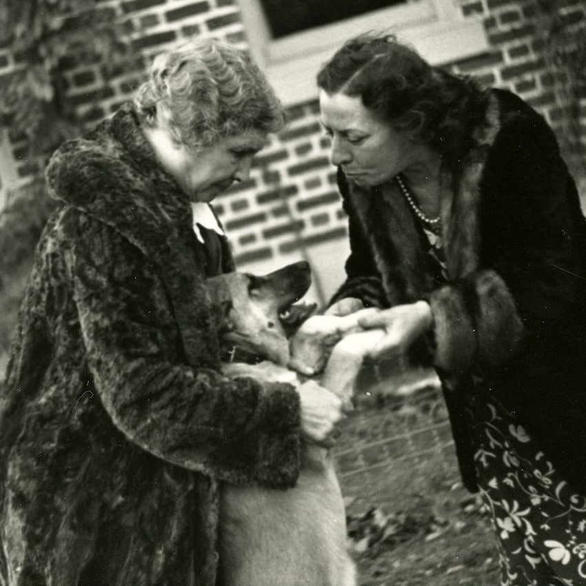 Helen Keller grips her dog Kamikaze, who leans back against her, while Polly Thompson leans forward to hold Kamikaze's paws.