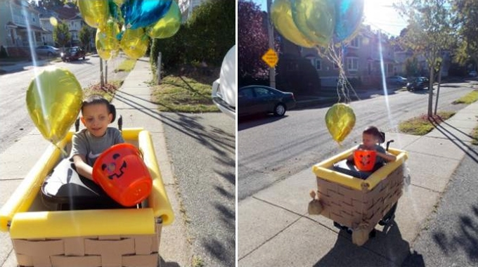 A boy dressed up for Halloween as a hot air balloon. The wheelchair was transformed into the basket of a hot air balloon using foam, cardboard and pool noodles.