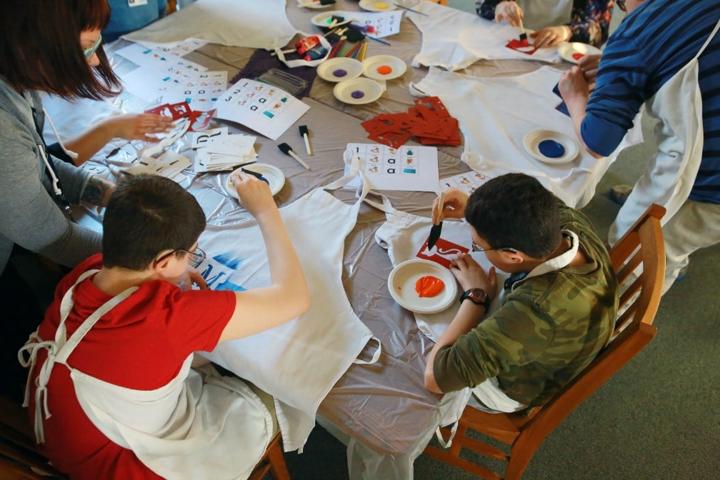 A group of students paints on aprons