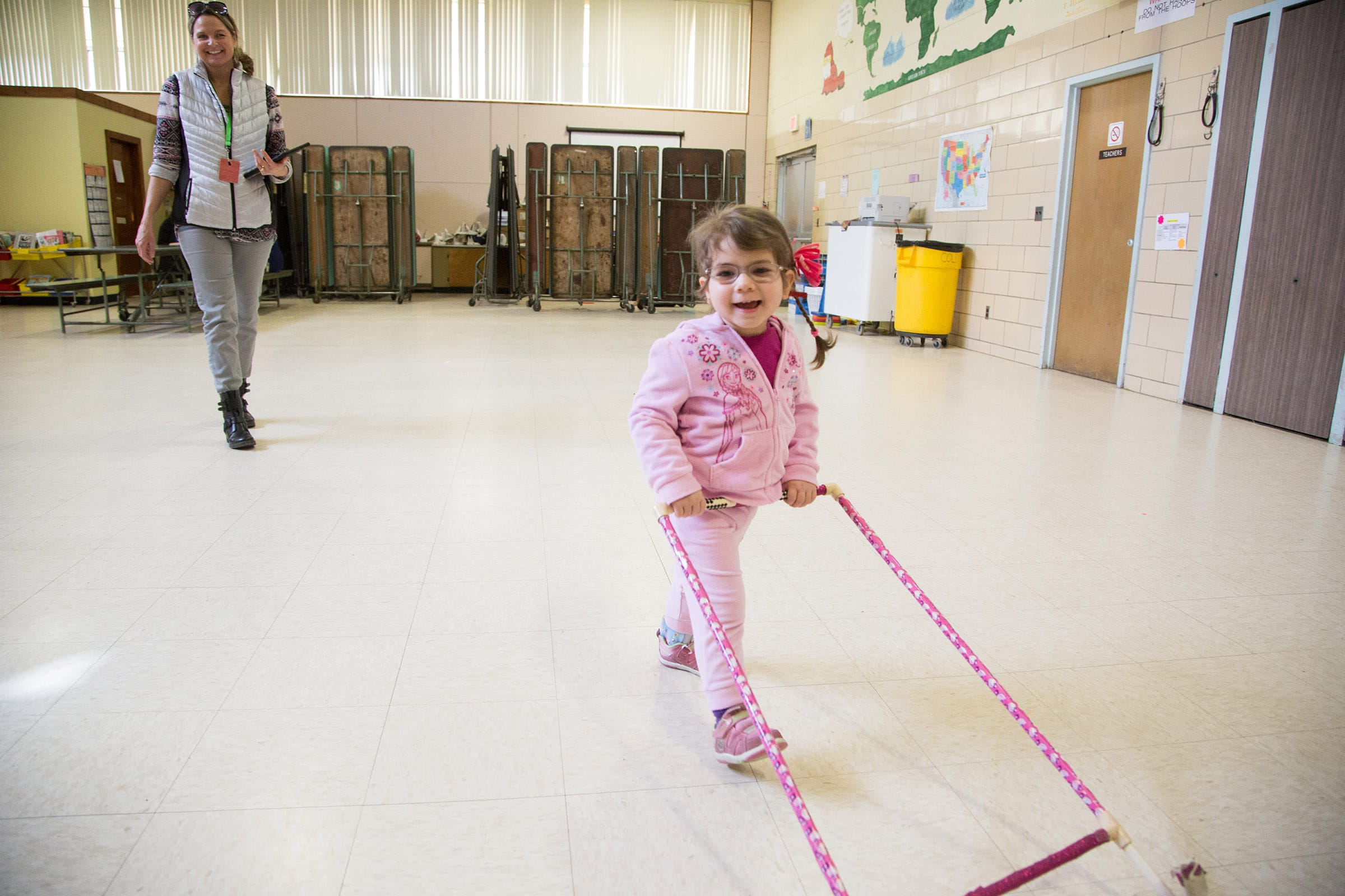 A young girl navigates her school during an orientation and mobility lesson with a teacher.