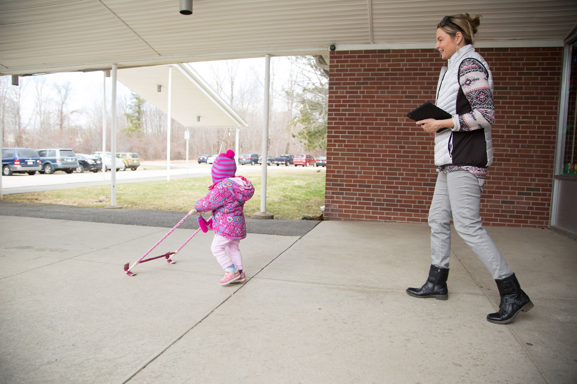 A young girl walks the school grounds independently.