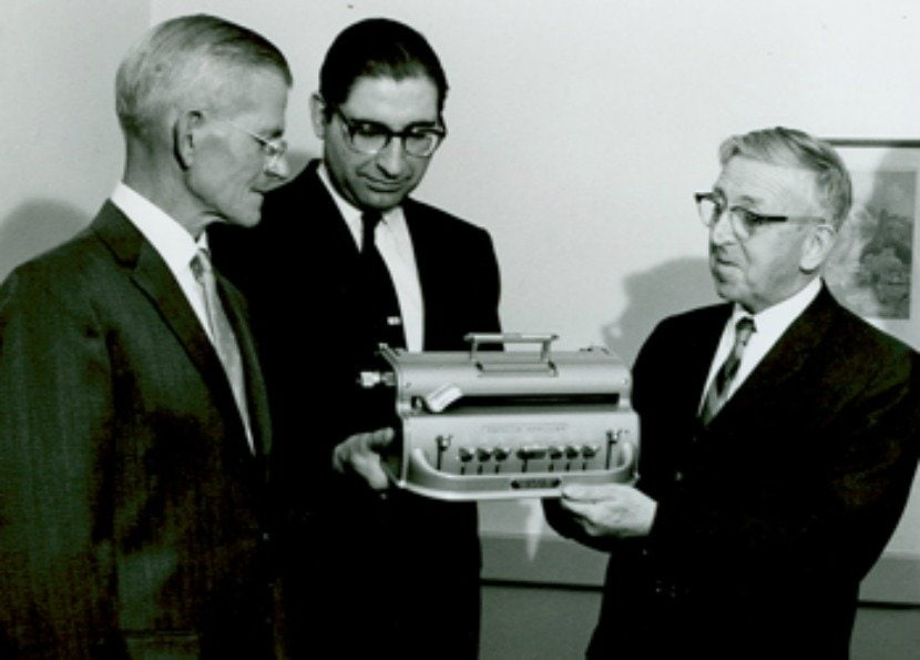 Perkins Brailler inventor David Abraham, Howe Press manager Harry Friedman and Perkins director Edward J. Waterhouse commemorate the production of the 25,000th Perkins Brailler in 1964.