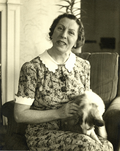Polly Thomson seated in an armchair, holding a dog in her lap at Forest Hills. The dog is nuzzling her leg.