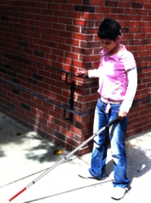 A Deafblind Program student walks with her white cane