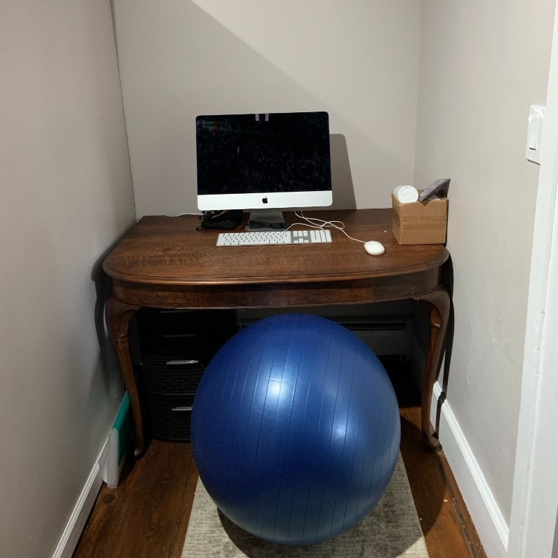 Desk in corner book with bare walls, computer on the desk, and a fitness ball used as a chair