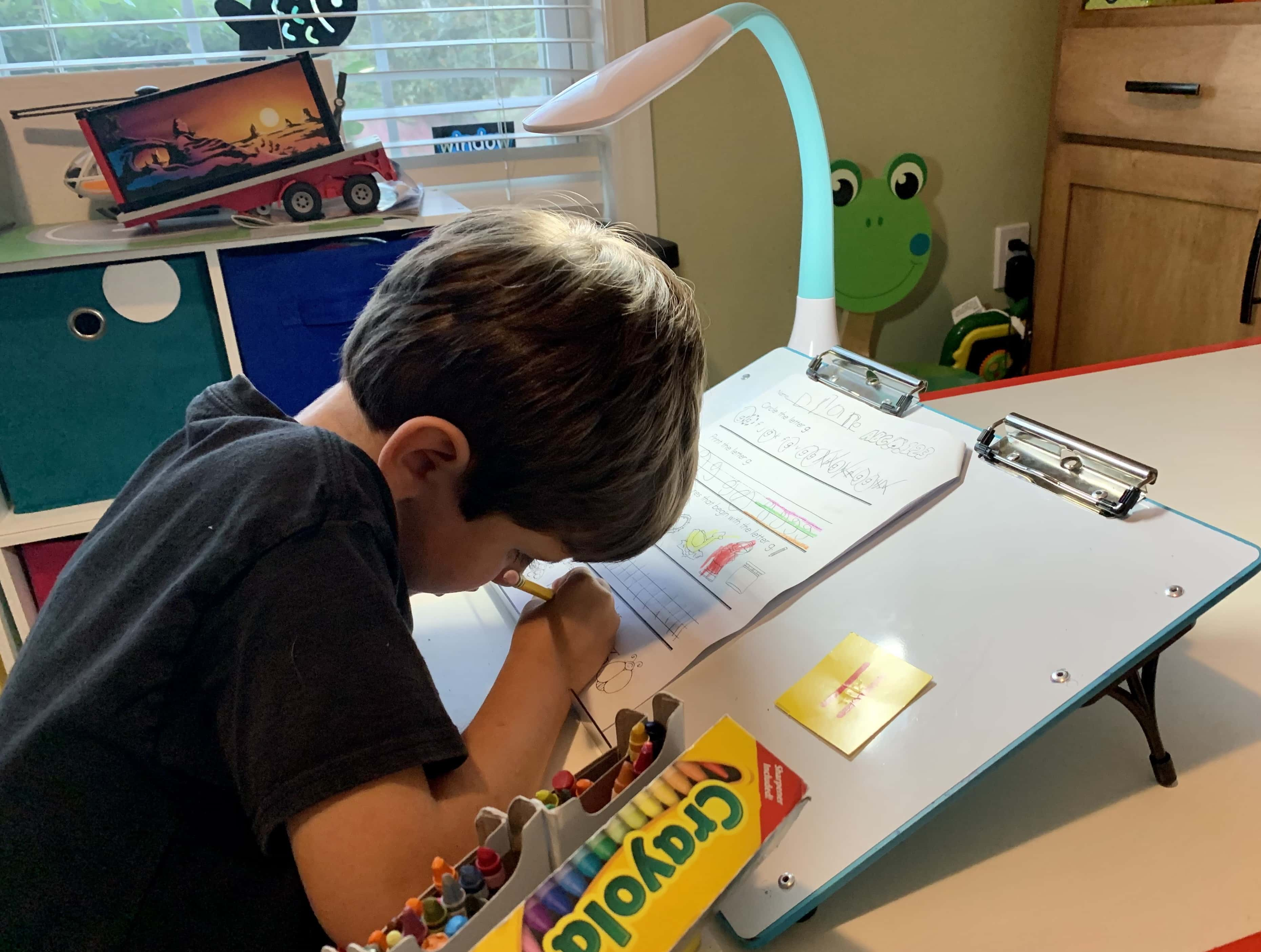 Boy with CVI writing on a slant board with a bright task light