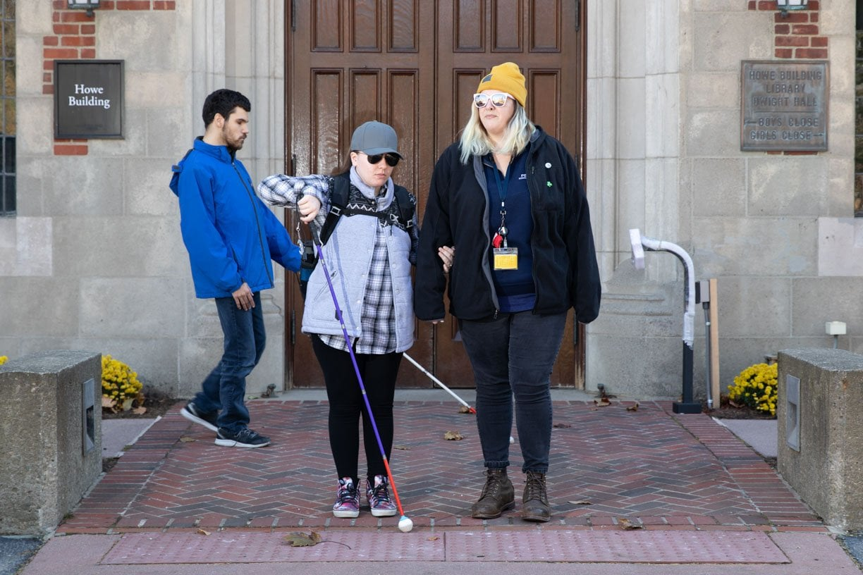 A student walks with a cane in one hand with the other on the teacher's arm as a guide. Another student walks behind them using a guide cane as well.