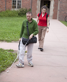 A male student walks through campus with a white cane