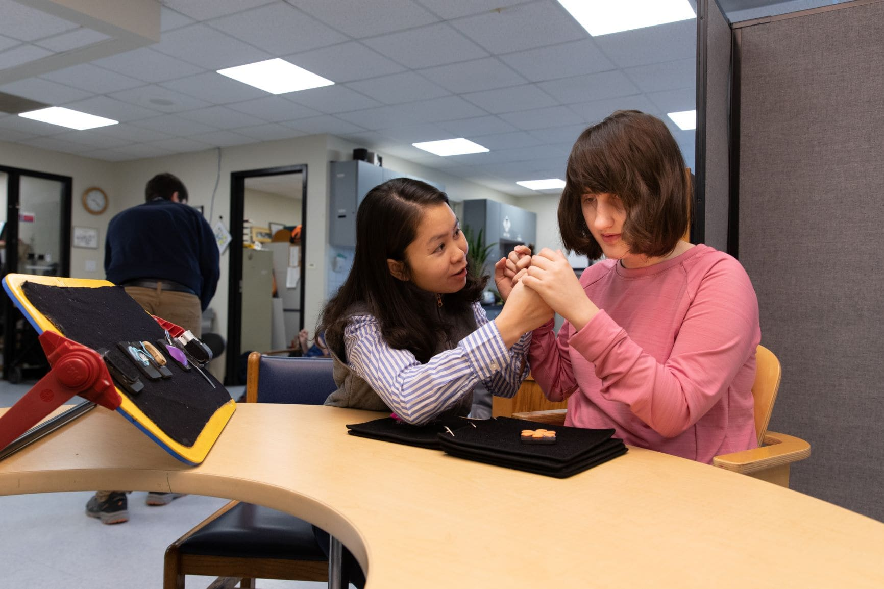 Thanh and Genna work with a tactile book, communicating with tactile sign language.