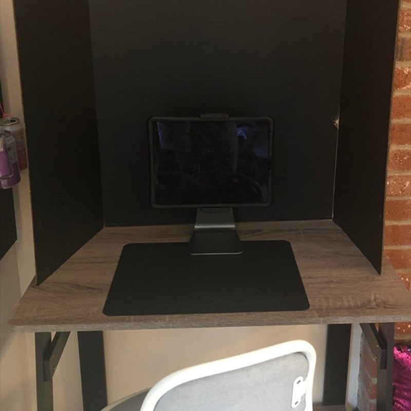 Desk with iPad on stand and a black trifold to block out visual clutter