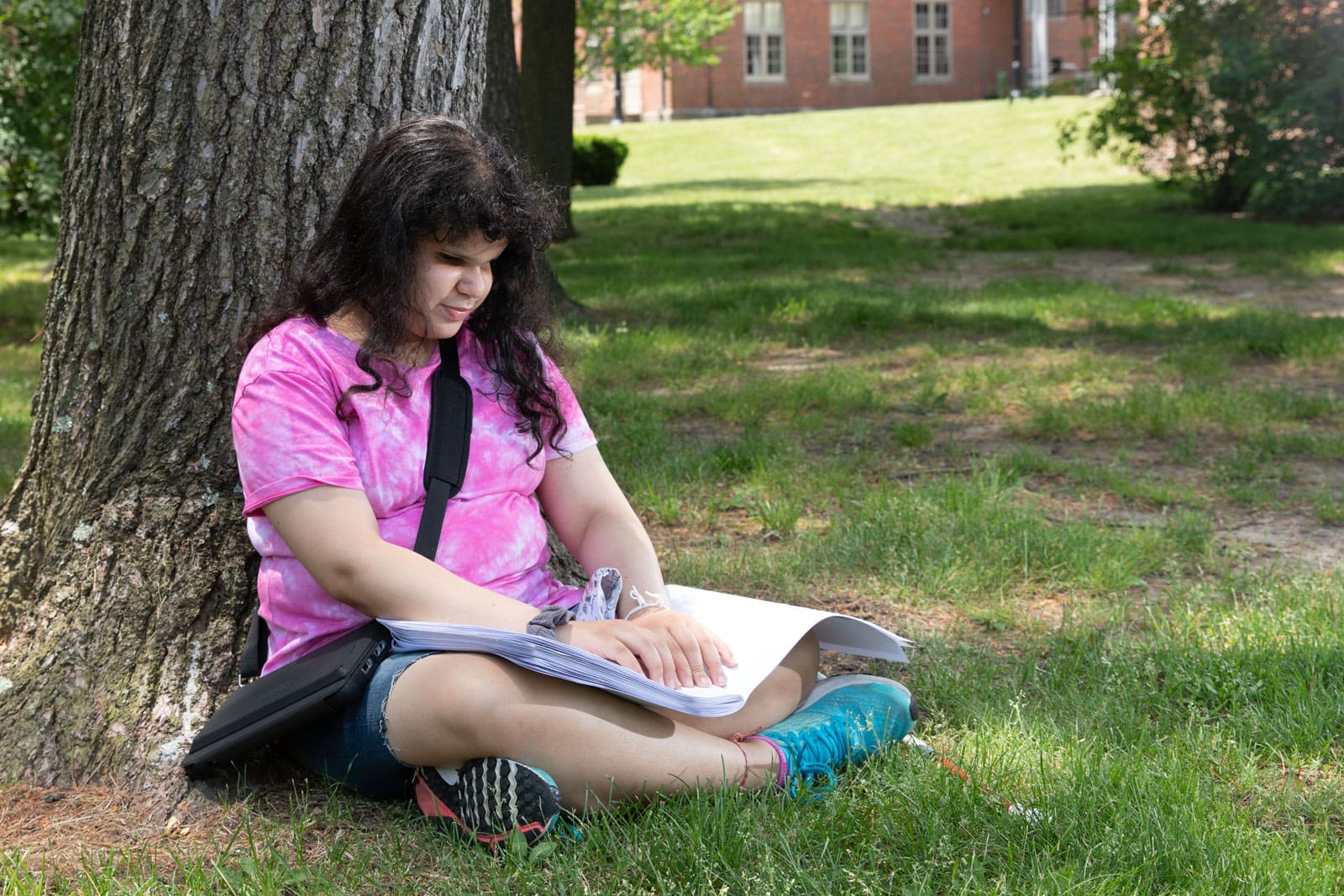 Eliz sits against a tree and reads a book in braille.
