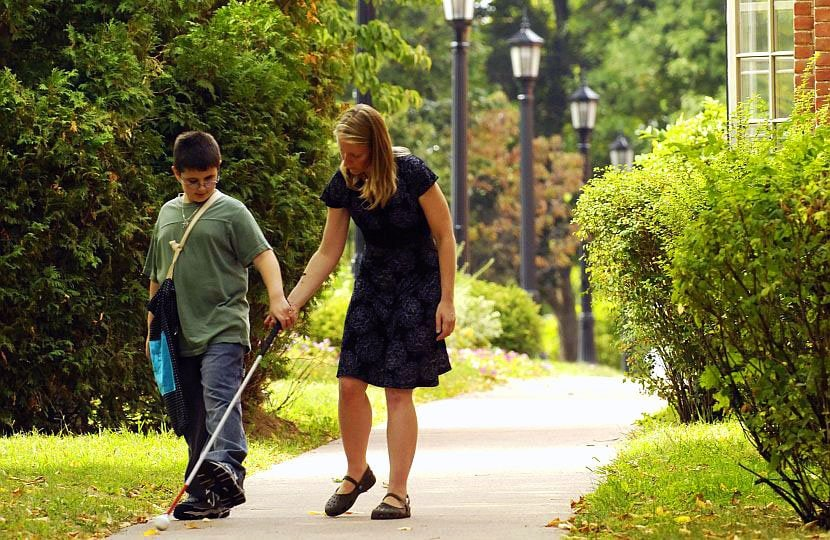 A women helping a visually impaired student walk with a cane outside.