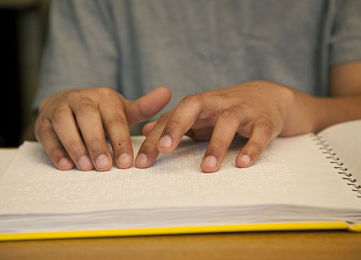 A child's hands reading braille.