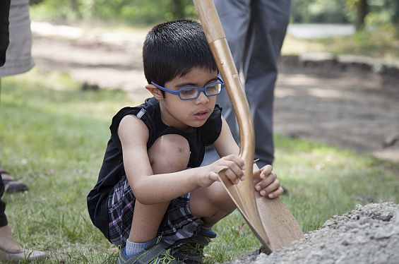 A boy holds the blade of a gold shovel as it digs into a mound of dirt.
