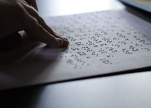 Fingers reading braille on paper