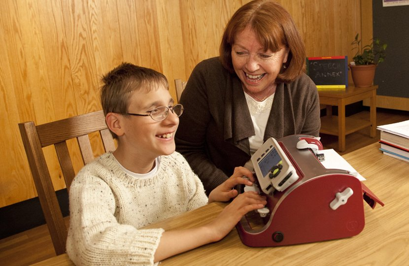 A older women helps a smiling young student use a smart brailler