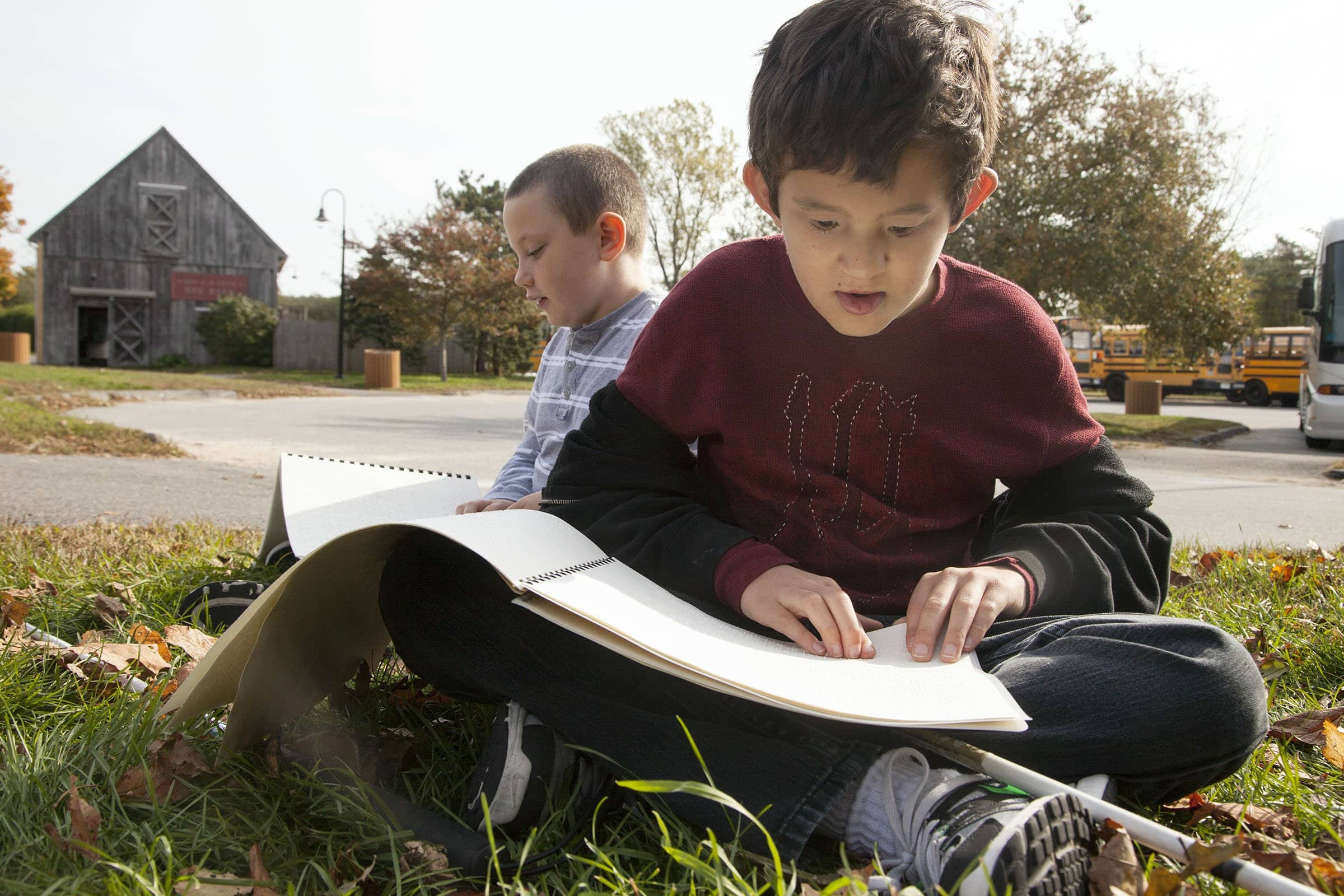A boy reads a braille book outside