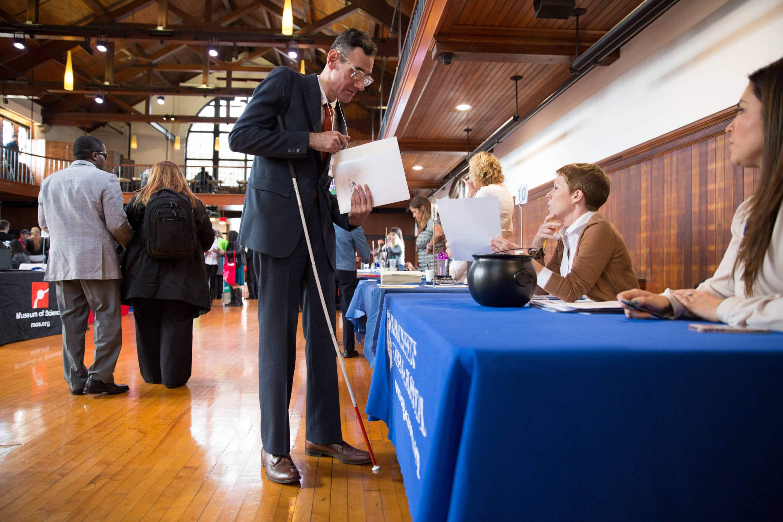 A tall man in a suit using his cane at a career event.