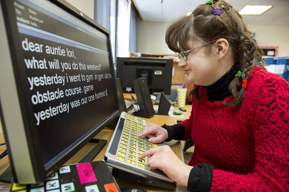 A girl uses a large print keyboard to type an email.