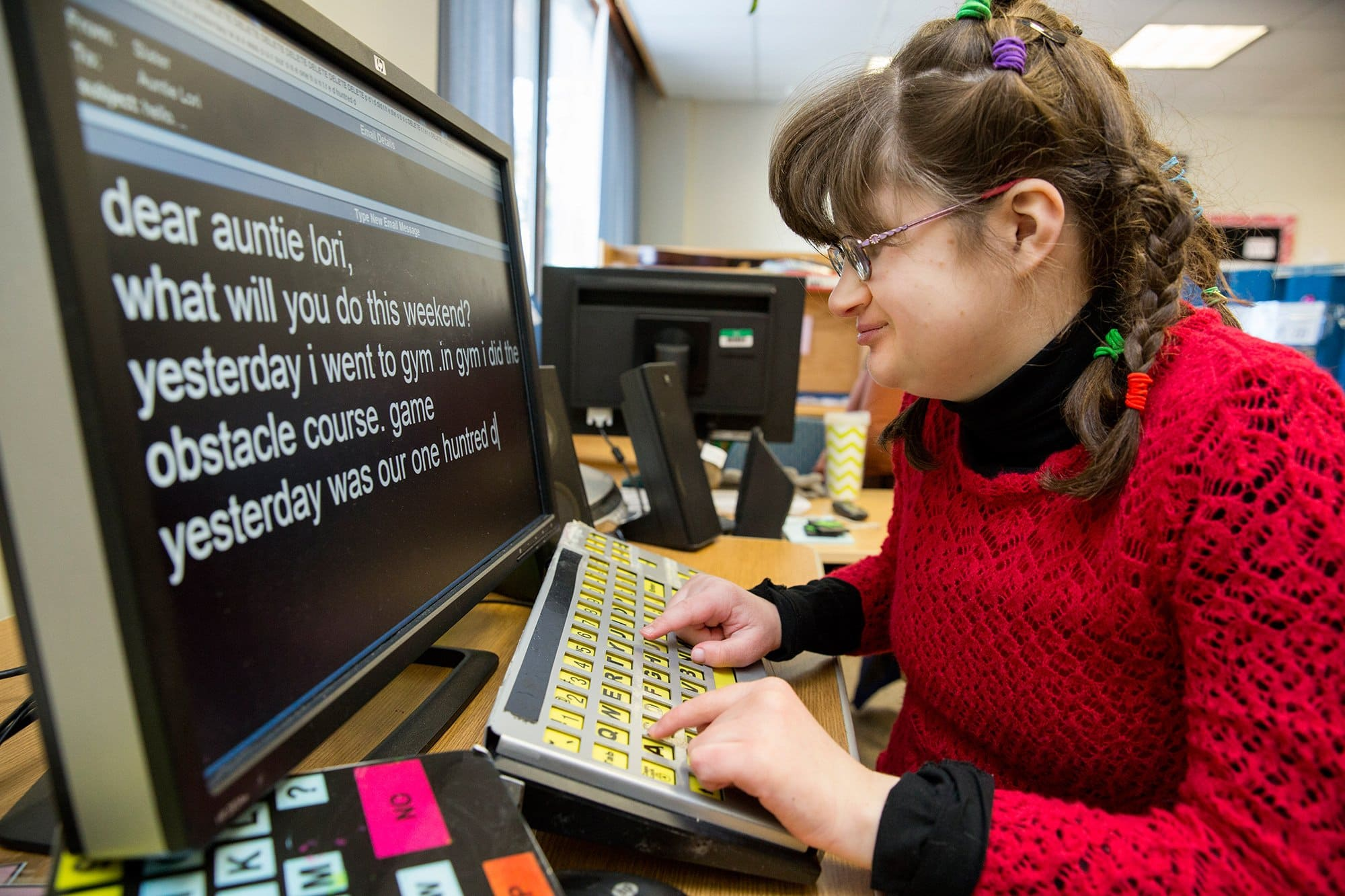 Slater, who is deafblind, types an email to her Aunt Lori. Photo Credit: Anna Miller