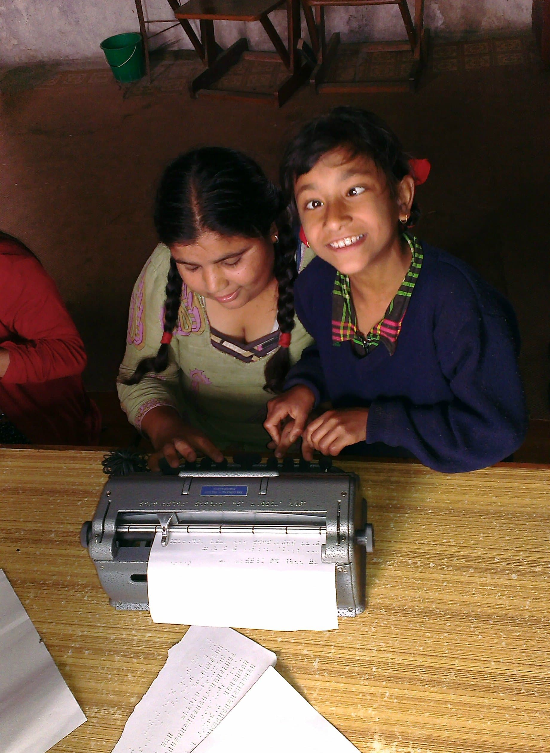 Two students in Nepal practice their writing skills using a Perkins Brailler.