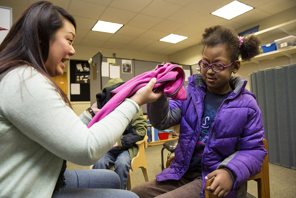 A girl reaches out to touch a pink fleece scarf.