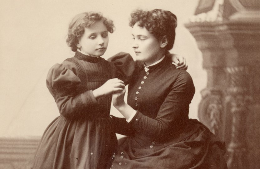 Anne Sullivan fingerspells into the hand of a very young Helen Keller in this black and white studio portrait circa 1888. Fingerspelling, a precursor to today's tactile sign language, is one of many methods Perkins has used over the years to help students who are deafblind connect with the world around them.