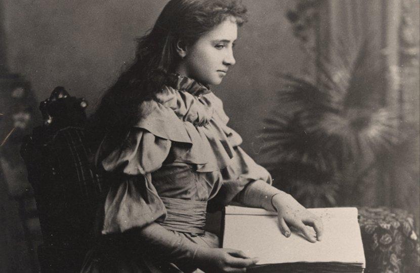 A young Helen Keller reading a braille book