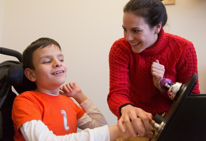 A little boy plays with a sensory board while a teacher looks on.