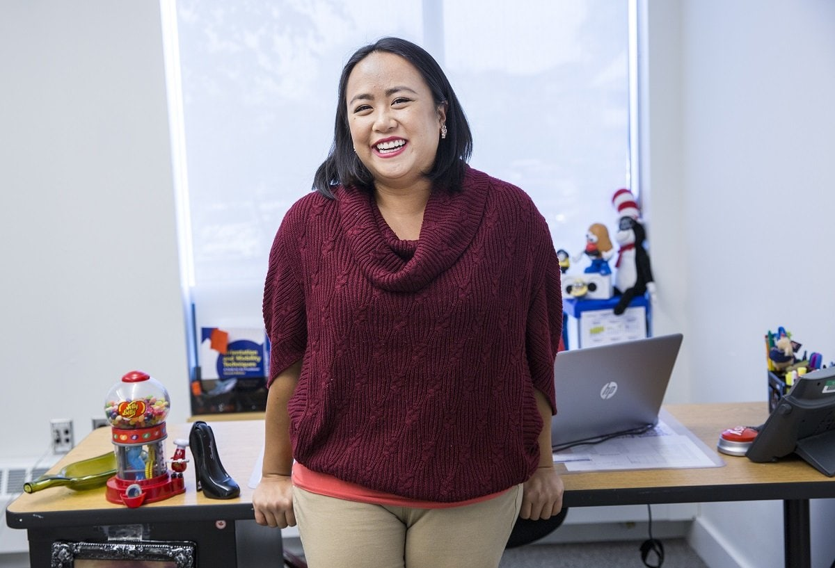 A woman standing in front of an office desk and smiling
