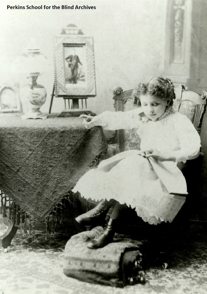Helen Keller as a young girl, sitting and reading. She is in a high-back cushioned chair, and has one hand resting on a table with the index finger extended. Her feet are propped up on a small ottoman. A vase and framed photograph are on the table. She is wearing a white lace dress.