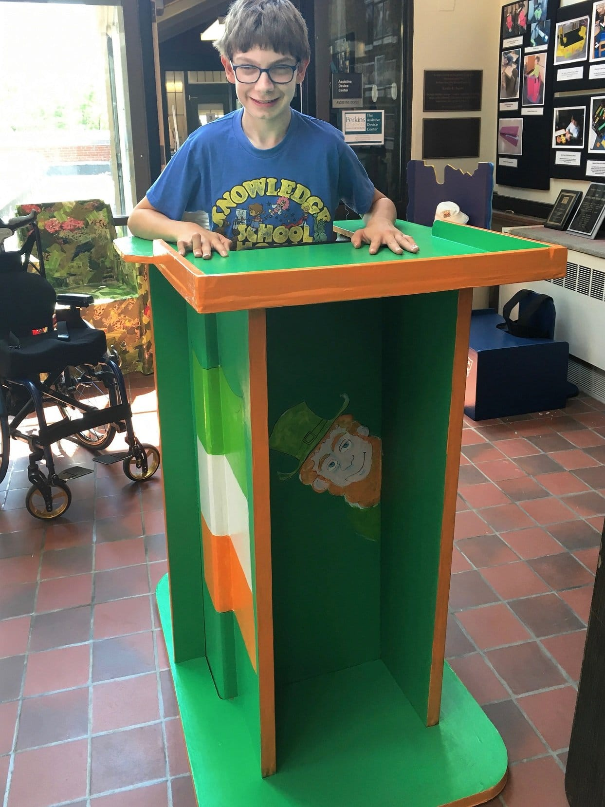 Aiden standing in his Irish-themed Standing Box at the Assistive Device Center.