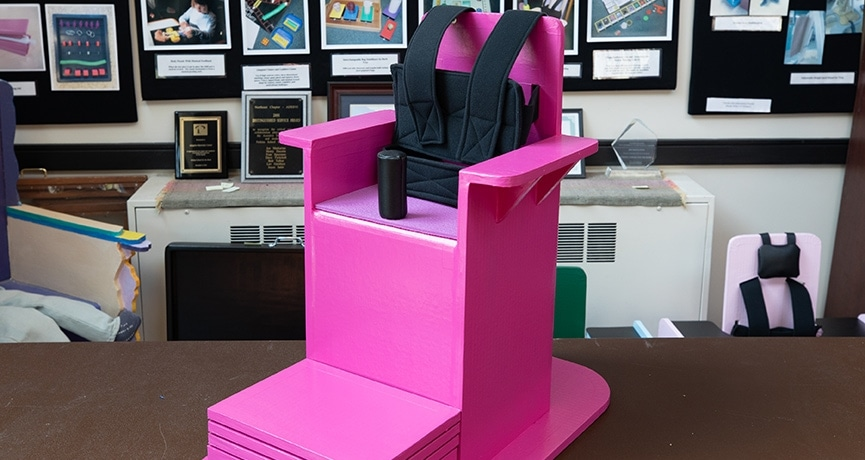 A pink adapted chair sits in a classroom.