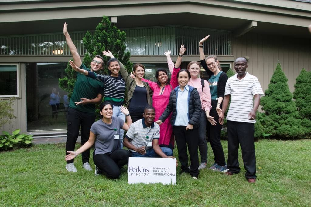 A group of individuals cheering behind a Perkins School for the Blind International sign.