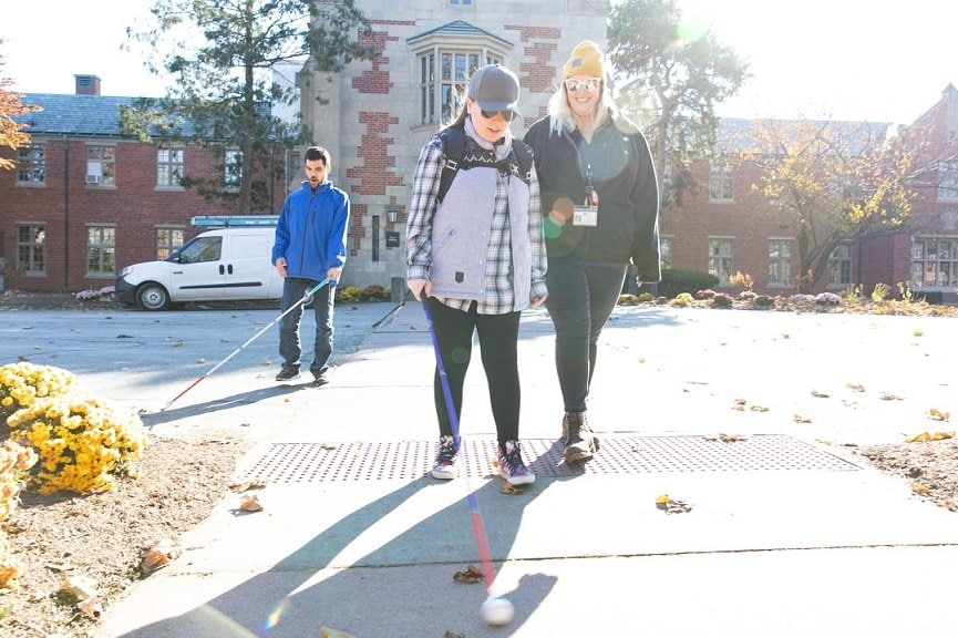 A Perkins volunteer walking with two visually impaired students outside in the fall.