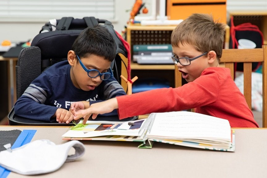 Zeke and Josian read from a tactile picture book during a Perkins Pals session.