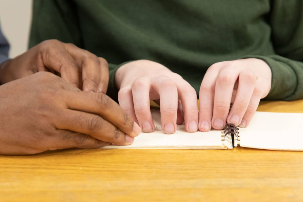 A closeup of two student's hands reading braille.