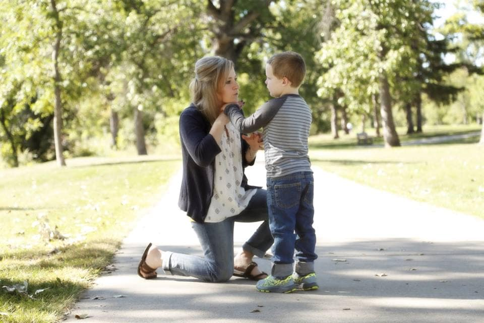 Adult kneels in front of child on park sidewalk and signs to him with her right hand under her chin. Child stands in front of her and feels her hands.