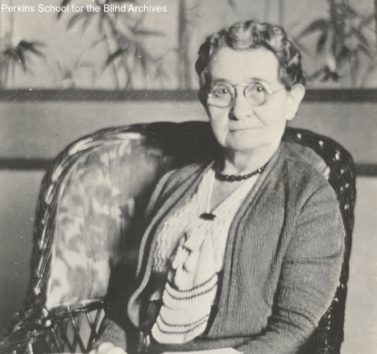 Seated portrait of Jessica Langworthy, circa 1936. There is a Japanese style artwork showing bamboo in the background. She is wearing a sweater and blouse. Langworthy has round wire-framed glasses on. Her hair is styled in finger waves.