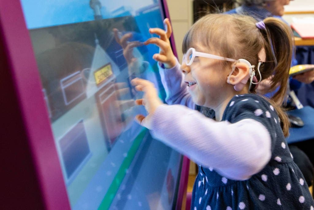 A young girl playing on a screen.