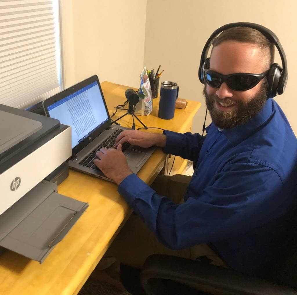 A man wearing headphones and dark glasses types on a laptop in an office