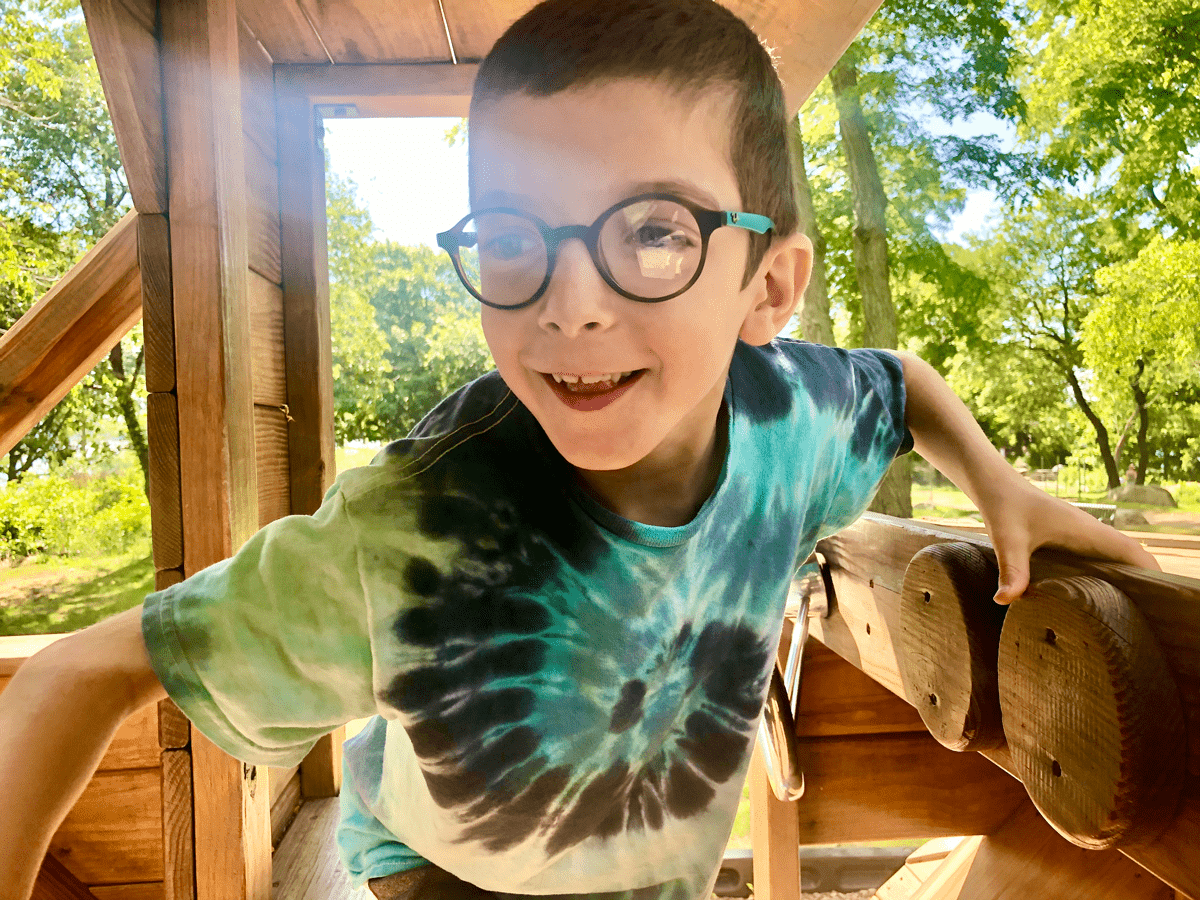 A visually impaired little boy playing outside on the playground with a smile on his face.